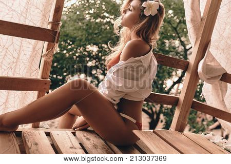Carefree and relaxed. Attractive young woman in swimwear relaxing while sitting in the tree house outdoors