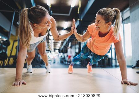 Two sporty girls doing push ups in gym together
