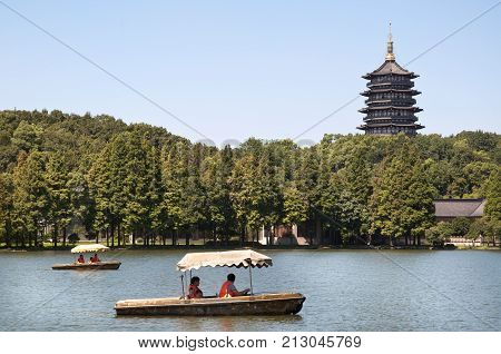 HANGZHOU, CHINA - JULY 29, 2012 - Leifeng Pagoda and tourist boats, West Lake, Hangzhou