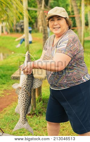 Elderly Fisherwoman Holding A Pintado Fish, Looking Forward And Smiling.