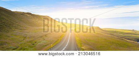 Highway Through Icelandic Landscape Under A Blue Summer Sky.