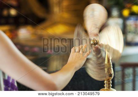 TAI WAI HONG KONG - SEPT 15 2013 - Worshipper at Che Kung Temple Tai Wai spinning a brass wheel of fortune