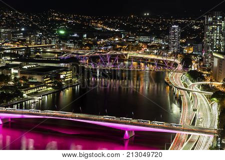 Aerial nightscape over Brisbane CBD, with a view of city traffic over Victoria Bridge and Pacific highway entrances into the city.