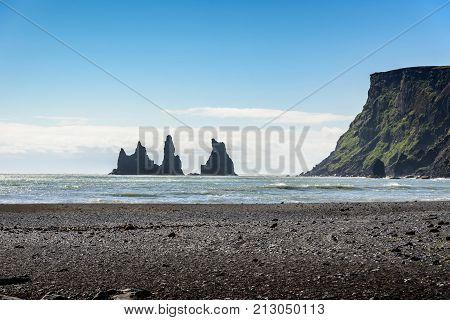 Beautiful Basalt rock Troll on black beach with blue sky Reynisdrangar Vik Iceland