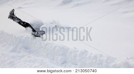 Man is falling headfirst and legs up in the air into deep snow. Winterly slippery conditions and dangerous accident concept.