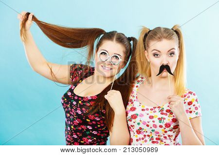 Two Women Holding Carnival Accessoies On Stick