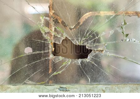 Smashed window pane with a hole in the middle