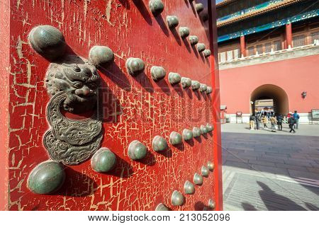 FORBIDDEN CITY, BEIJING - FEB 6, 2015 - Lion design on a red wooden door leading to the northern gate of the complex, the Gate of Divine Might.
