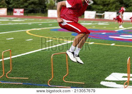 A high school football player is jumping orange hurdles at a preseason football practice on a green turf field.