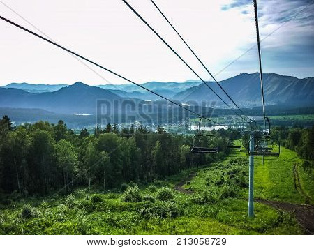Emtpy chairlift in ski resort. Shot in summer with green grass and no snow. Smoke on the mountains.