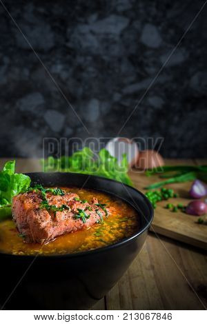 Tomyum salmon in black blow and knife peper vegetable on chopping board on wooden table