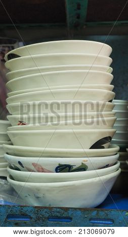Ceramic bowls stacked prepare for use on shelf at Boat noodle old shop in Thailand Concept vintage Asian style.