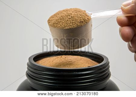 A cup of whey protein powder for muscle gains or diet person is in a plastic bottle on white background.