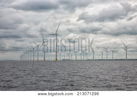 Large offshore windfarm near Dutch coast with cloudy sky. This park in the lake IJssselmeer near Urk is the biggest windfarm of the Netherlands