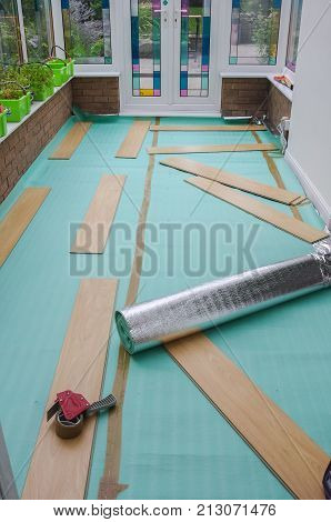 Laying laminate flooring. Insulated underlay on floor ready for the click lock wood effect laminate flooring to be laid. DIY project in a domestic home conservatory.