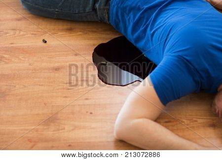 murder, kill and people concept - dead man body in blood lying on floor and bullet sleeves at crime scene