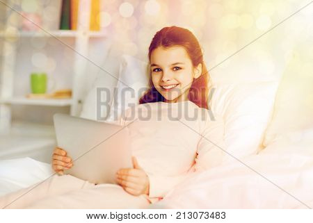 people, children and technology concept - happy smiling girl lying awake with tablet pc computer in bed at home