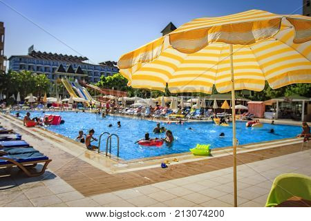 Swimming pool in tropical resort hotel. Yellow umbrella on blurred background of bathing tourists in pool on bright sunny day on vacation.
