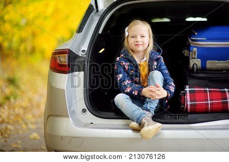 Adorable Girl Sitting Ain A Car Trunk Ready To Go On Vacations With Her Parents. Child Looking Forwa