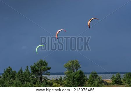A kite surfer rides on the sea. Kites in the sky. Kite Boarding extreme sport on Mohni small island in Estonia Europe.