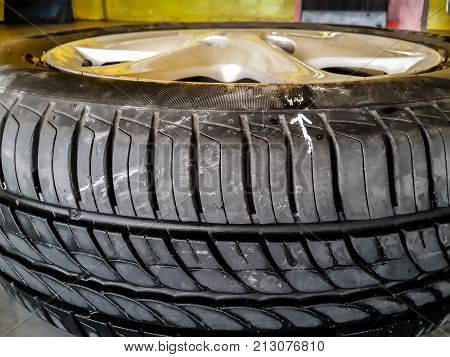 white arrow mark the leaking point on car tire. sometimes the leaking can not be seen with bare eyes tire must be checked by putting under water and see air bubble and mark the position for repair.