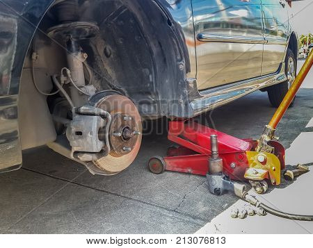 Car on jack lift with one tire removed reveal the rusty disc brake. Tire replacement on road side.