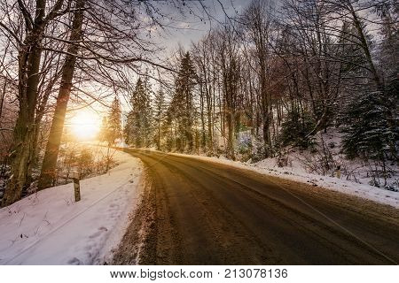 Asphalt Road Through Winter Forest At Sunset