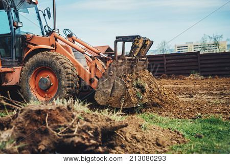 Close Up Of Industrial Bulldozer Moving Earth And Leveling Garden