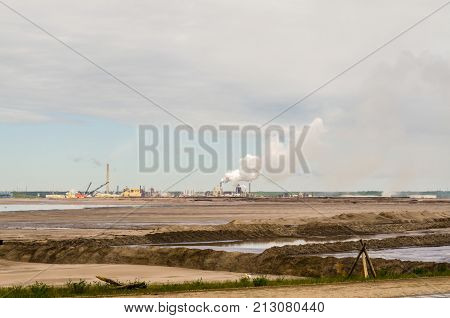 The largest Canadian oil refinery in the background oil sand in the foreground smoking pipes