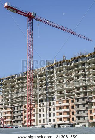 High-altitude crane on a background of monolith-brick house and blue sky.