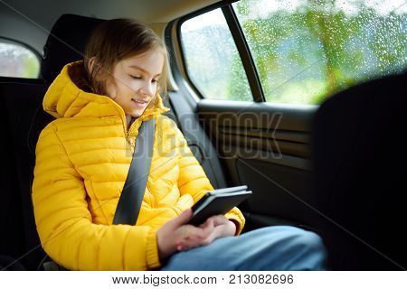 Adorable Girl Sitting In A Car And Reading Her Ebook On Rainy Autumn Day. Child Entertaining Herserf