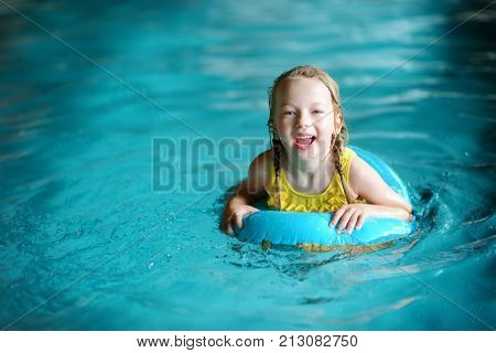 Cute Little Girl Playing With Inflatable Ring In Indoor Pool. Child Learning To Swim. Kid Having Fun