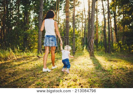Beautiful And Stylish Mother Leads The Hand Of A Girl Of One Year From Birth In The Park Against The
