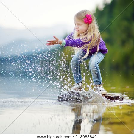 Adorable Girl Playing By Hallstatter See Lake In Austria On Warm Summer Day. Cute Child Having Fun S