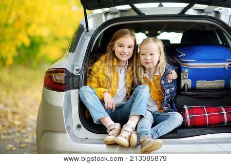 Two Adorable Girls Sitting In A Car Trunk Before Going On Vacations With Their Parents. Two Kids Loo