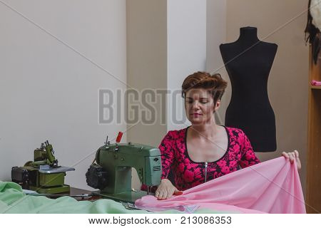Young female dressmaker choosing material from catalogue in studio. Tailor looking through fabrics while standing in a sewing workshop