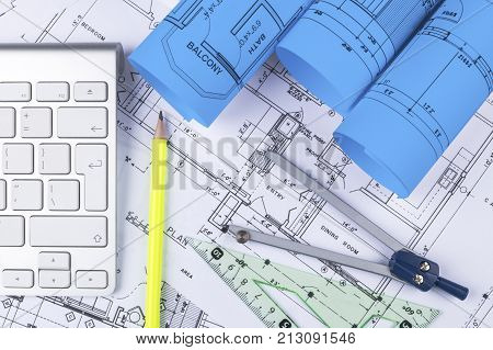 Architectural blueprint drawings of the modern house with computer keyboard. Architectural blueprints and blueprint rolls and a drawing instruments on the worktable. Drawing compass plans.