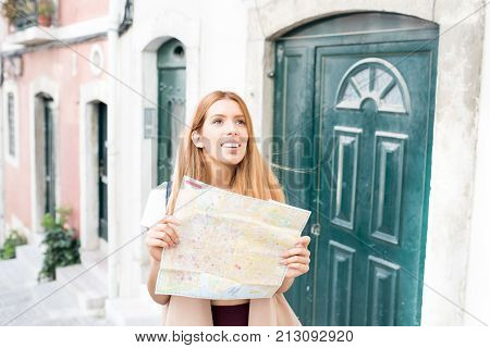 Happy attractive girl planning route in city and choosing sightseeing. Inspirited young tourist with paper map looking into distance while finding street. Guide tour concept