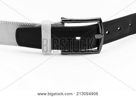 Black leather belt is inserted into the buckle of the white belt on a light background