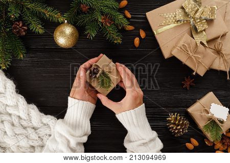 Preparation christmas gifts on a black wooden table with fir branches