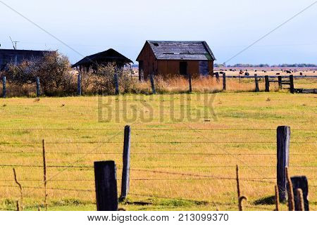 Forgotten abandoned ranchland surrounded by a broken collapsing fence taken in a rural prairie