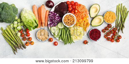 Healthy eating concept, above view of rainbow buddha bowl, various vegetables, carrot, courgette, cabbage, chickpeas, cucumber and tomatoes, on wooden board on white table, long photo, selective focus