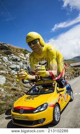 Col de la Croix de Fer France - 25 July 2015: The famous LCL Yellow cyclist mascot on the road to the Col de la Croix de Fer in Alps during the stage 20 of Le Tour de France 2015. LCL was the largest bank in France and sponsored continuosly the TDF.