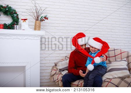 Two cute boy-brothers on the couch, wearing Santa's hats. The younger brother sits on the lap of the elder. Nearby fireplace on which there is a Christmas wreath.
