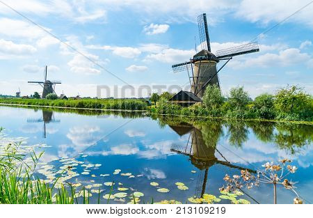 Windmills across and reflected in water in Kinderdijk district popular tourist destination with it's scenic fields dykes ponds canals and windmills near Rotterdam Holland.