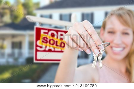 Excited Woman Holding House Keys and Sold For Sale Real Estate Sign in Front of Nice New Home.