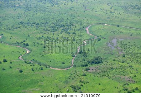 Aerial of savannah type vegetation in Africa, with a river, shot over South Sudan in the rainy season