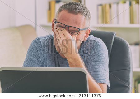 Tired freelancer man rubbing his eyes while working with laptop