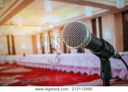 Microphones on abstract blurred of speech in seminar room or front speaking conference hall light white chairs for people in event meeting convention hall in hotel.