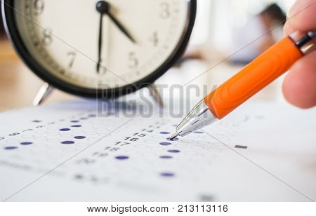 Asian Students taking optical form of standardized exams near Alarm clock with hand holding yellow pen for final examination in secondary school college university classroom Education concept